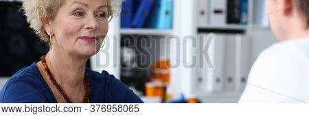 Happy Elderly Woman Measures Pressure At Doctor. High-quality Procedures In Diagnostic Center. An El
