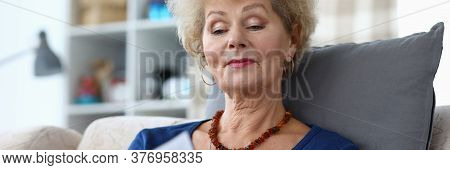 Portrait Of Concentrated Smiling Female Reading Hardcovered Book. Good-looking Attractive Senior Wom