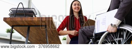 Portrait Of Cheerful Smiling Company Manager Interviewing Candidate On Vacancy. Disabled Man Sitting