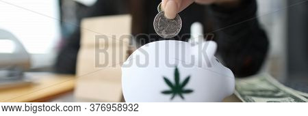 Close-up Of Female Hand Putting Money To White Piggy Bank With Marijuana Sign. Woman Holding Silver