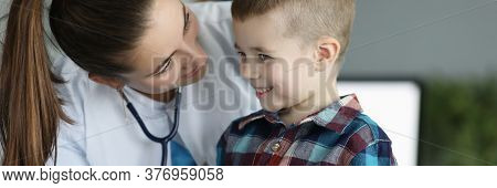 Close-up Of Smiling Kid At Doctors Appointment. Professional Pediatrician Listening To Heartbeat And