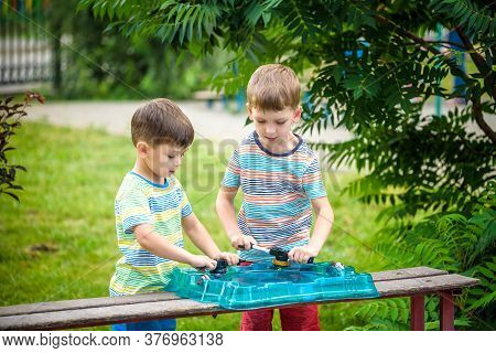 Two Boys Playing With A Spinning Top Kid Toy. Popular Children Game