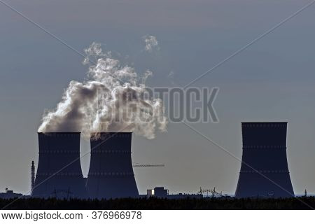 Parabolic Cooling Towers Are Represented By Their Silhouettes Against The Setting Sun, Which Illumin
