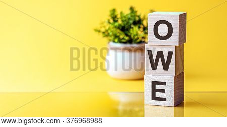 Word Owe Made With Wood Building Blocks, Yellow Background