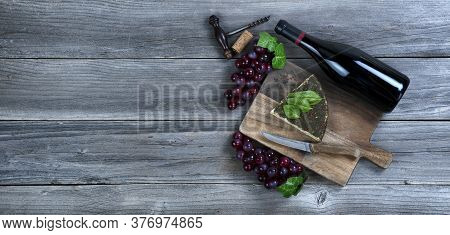 Fresh Cheese Wedge With A Bottle Of Red Wine Plus Basil Leaves And Grapes On Rustic Wood With Copy S