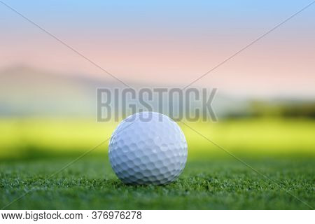 Golf Ball On Green In Beautiful Golf Course At Sunset Background. Golf Ball On Green In Golf Course