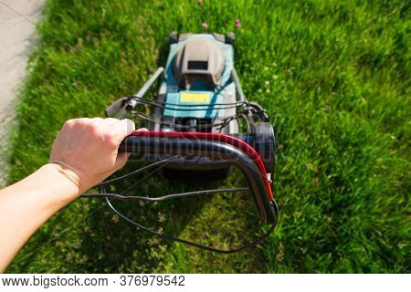 A Man Mows A Green Lawn With A Makita Electric Lawn Mower. The Concept Of Working In The Garden, A B