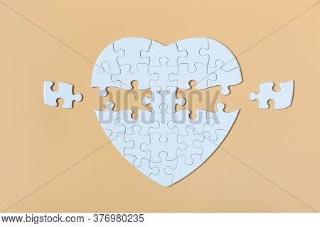 White Jigsaw Puzzle On The Yellow Background. Completing Final Task, Missing Jigsaw Puzzle Pieces An