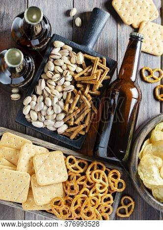 Beer In Glass Bottles And Salty Snacks For Beer. Brown Wooden Background. The Concept Of A Party For