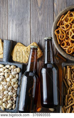 Beer In Glass Bottles And Salty Snacks For Beer In Wooden Dishes. Rustic Style. Brown Wooden Backgro