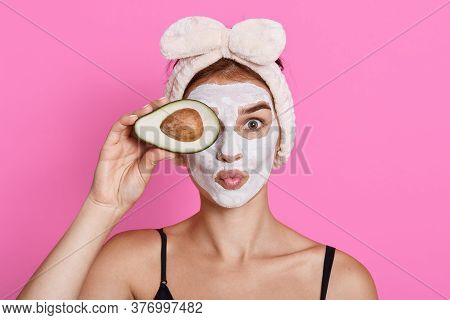 Cheerful Woman With Cosmetic Mask On Face, Doing Spa Treatment, Covering Eye With Half Of Avocado, K
