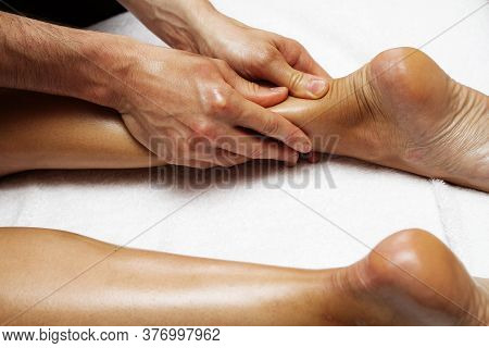 Female Feet Close Up. Photo Of Massage Of Legs And Feet. Male Hands Of A Masseur.