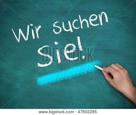 Hand writing wir suchen sie on blue background