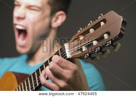 Young Guitar Player Performing Over Gray Background