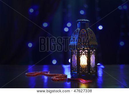 Ramadan lantern and rosary on dark background
