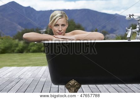 Portrait of a beautiful woman in bathtub on porch against mountains
