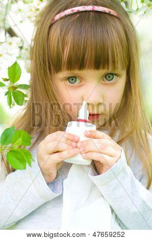 Little girl spraying medicine in nose nose drops nose spray. poster