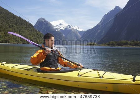 Young man kayaking in peaceful lake with mountains in background