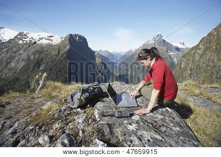Side view of a young woman using laptop on boulder against mountains