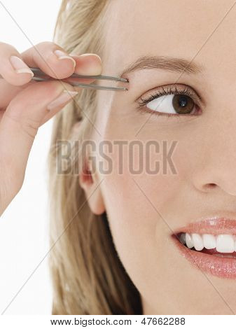 Closeup cropped shot of a young woman plucking eyebrow against white background