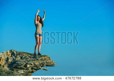 acrophobia tall woman stands on top of a rock cliff edge and is