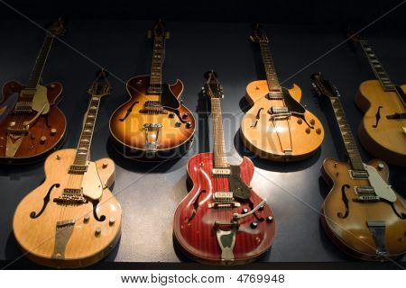A wall with vintage guitars hanging on display. poster