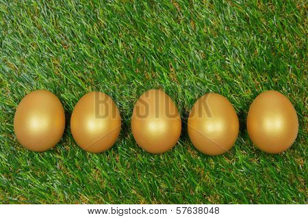 Five Golden Eggs On A Green Artificial Turf