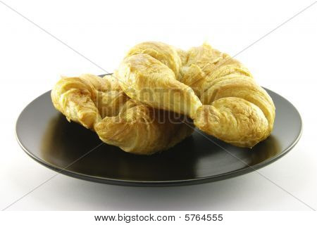 Two Croissants On A Black Plate