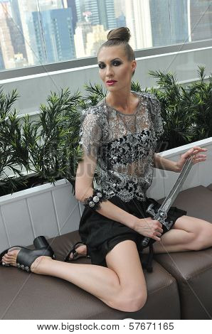 Model wearing couture clothes and holding sward