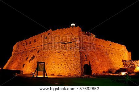 Tower Of St. Nicholas In Rhodes (greece) By Night - Bluelight. Motion Blur On Greek Flag And Sail Ma
