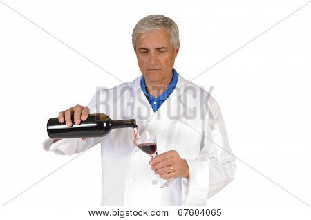 older sommelier pouring red wine into a glass, isolated on white.