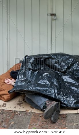 Homeless man curled up asleep under a plastic tarp on the street. poster