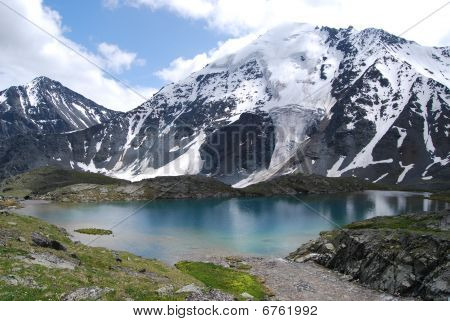 Blue Lake In Front Of Snowed Hills