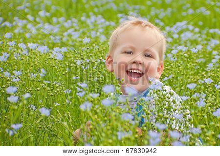 A smiling boy on green floor.