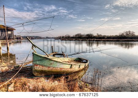 landscape at morning with abandoned boat and fishing shacks in the river of Ravenna Italy poster