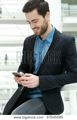 Young Man Dialling On Mobile Phone