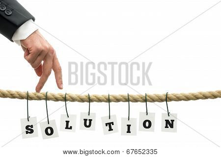 Businessman walking his fingers along a frayed rope wit sign Solution hanging off it. Conceptual of overcoming problems. poster