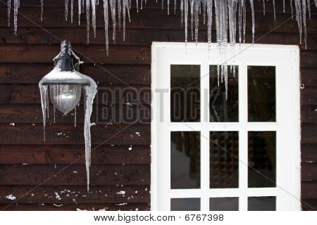 Icicles On The Exterior Of A Panelled Wooden House