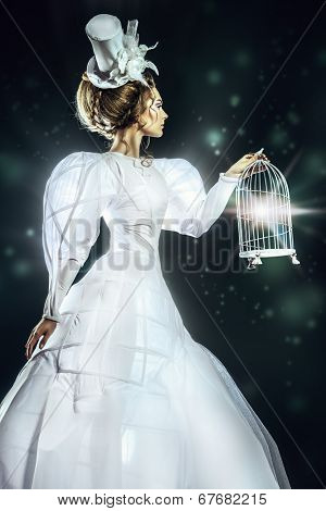 Portrait of a beautiful fashion model in the refined white dress and elegant hat holding birdcage. Black background.