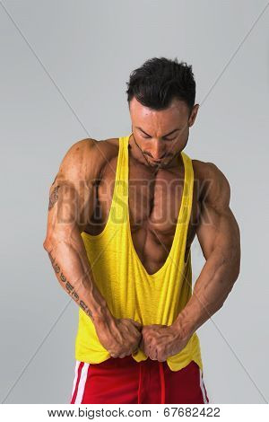 Muscular Man Pulling Down Tanktop On Torso