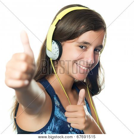 Beautiful hispanic teenager listening to music on her headphones while doing a thumbs up sign isolated on white