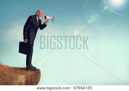 Senior Businessman Yelling Through A Loudhailer