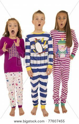 Three Children Wearing Winter Pajamas With A Startled Facial Expression