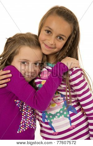 Two Cousin Girls Wearing Christmas Pajamas Hugging Each Other