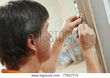 worker carpenters at wooden  internal door lock installation