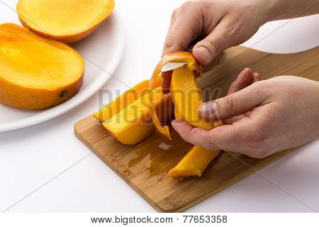 Hands Separating Mango Fruit Flesh From Its Skin