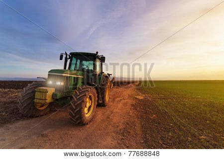 Tractor On Field At Sunset After Plowing