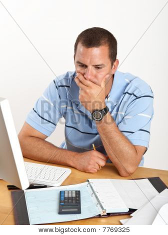 Worried Young Businessman At Desk