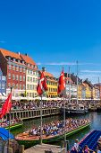 COPENHAGEN DENMARK - JULY 25: Nyhavn district is one of the most famous landmark in Copenhagen. People enjoy sunny weather in open cafees in Copenhagen on July 25 2014 poster