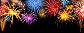 Gorgeous multi-colored fireworks display on black night sky with freely extendable copyspace poster
